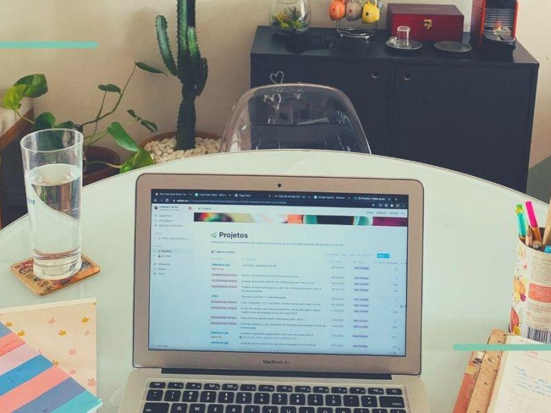 """Foto de mesa com notebook aberto em tela do Notion onde se lê """"Projetos"""""""
